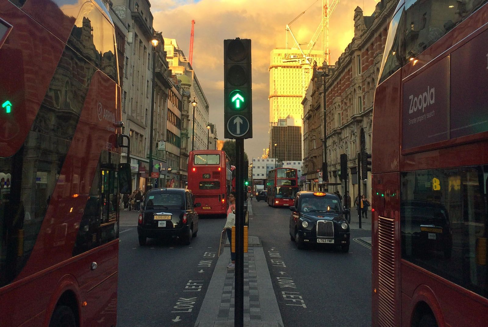 Buses and taxis in a London street at dusk