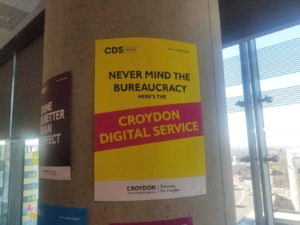 "Pillar in office with poster: ""Never mind the bureaucracy, here's the Croydon Digital Service"""