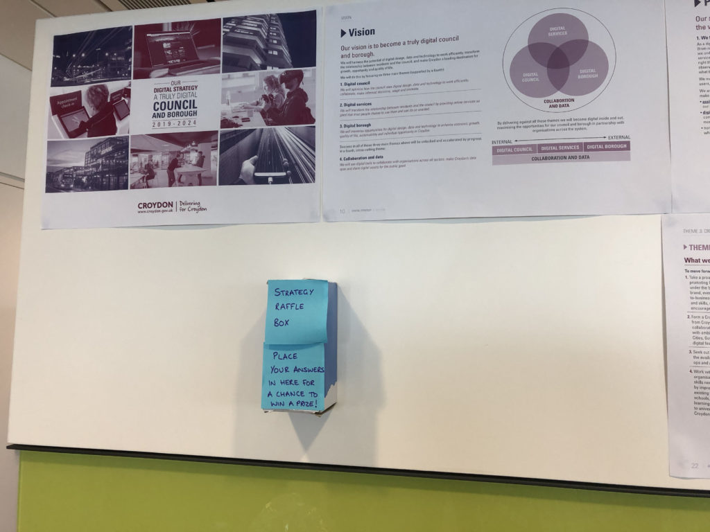 Office wall with poster explaining the Croydon Digital Strategy 'vision', with a 'strategy raffle box' underneath.