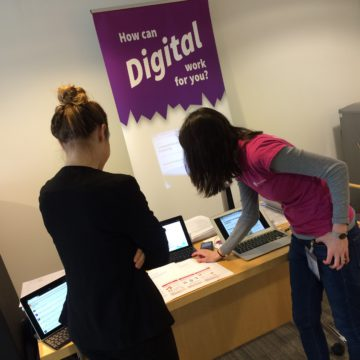 "Two women looking at a computer screen next to a stand banner that reads ""How can digital work for you?"""